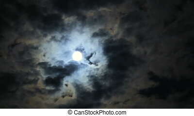 Scary Full Moon and Dark Clouds at Night. Scary Full Moon in...