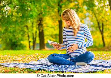 Pregnant girl reading notes in a notebook is preparing to...