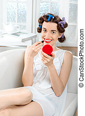 Smiling woman with hair curlers using lipstick on white...