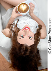 Young woman relaxing at home - Young woman with coffee cup...