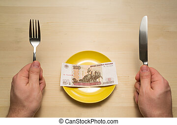 Plate with hundred rubles copyspace - hands holding knife...