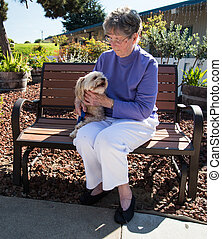 Elderly woman and dog on bench