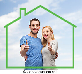 smiling couple showing thumbs up over green house - love,...