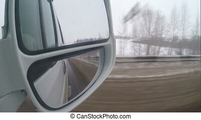 Winter road, the view in the rearview mirror