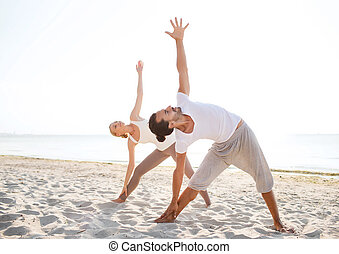 couple making yoga exercises outdoors - fitness, sport,...