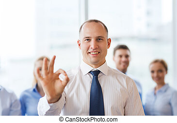 smiling businessman showing ok sign in office - business,...