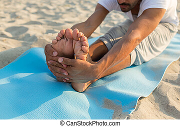 close up of man making yoga exercises outdoors - fitness,...