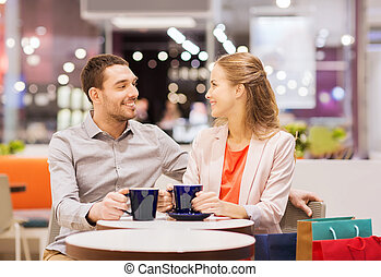 happy couple with shopping bags drinking coffee - sale,...