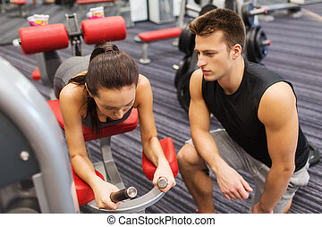 young woman with trainer exercising on gym machine - sport,...