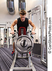 young man exercising on t-bar row machine in gym - sport,...