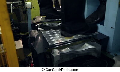 View of machine heats rubber sole for boots, close-up