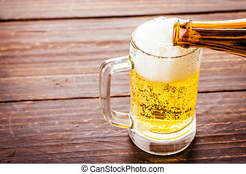 Beer glass on wooden background - Vintage effect style...