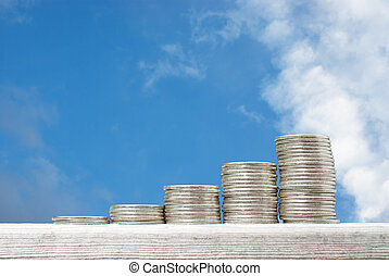 Business concept with stacks of coins against blue sky...