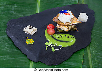 Fried fillet of white fish and vegetables on a black stone instead of plate
