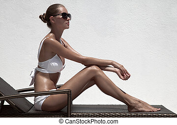 Beautiful tan female model sunbathing in bikini on...
