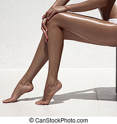 Beautiful woman tan legs Against white wall