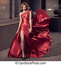 Young Beautiful Woman In Fluttering Red Dress. City...