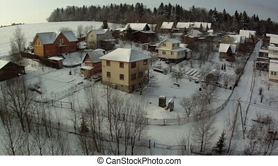 View from hot air balloon of cottage village in winter