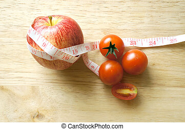red apple and tomatoes wrapping with tape measure (diet concept)