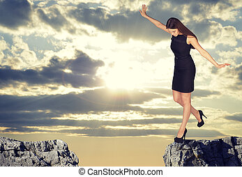 Businesswoman standing on the edge of rock gap -...