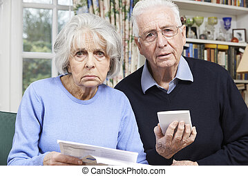 Senior Couple At Home With Bills Worried About Home Finances
