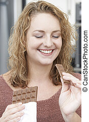 Plus Size Woman Enjoying Eating Bar Of Chocolate