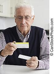 Senior Man Reading Information On Drug Packaging