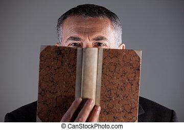 mature man behind an ancient book staring at camera