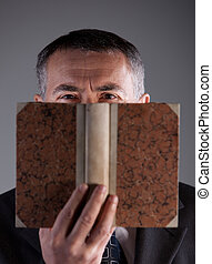 mature man behind an ancient book staring at camera