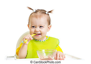 Happy baby eating with spoon sitting at table isolated