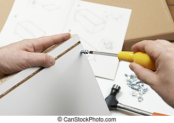 Close Up Of Man Assembling Flat Pack Furniture With Screwdriver