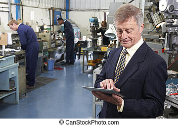Owner Of Engineering Factory Using Digital Tablet With Staff...