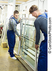 Two workers in uniform inspecting windows at workshop