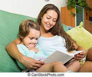 Mother and child reading book - Young mother and daughter...