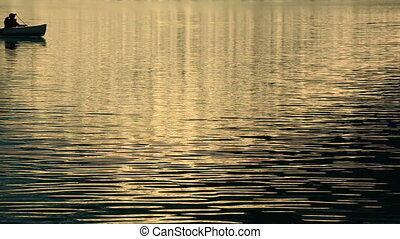 Canoe on Alpine Lake - Single canoe passes through frame in...