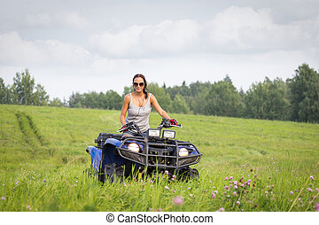 Elegant woman riding extreme quadrocycle in summer fields