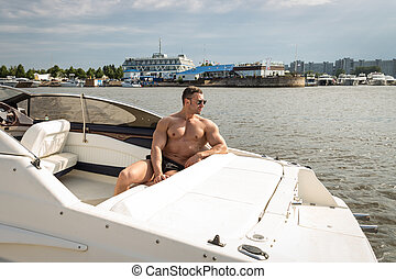 Muscle man on a boat summer time