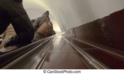 Escalator with people in the subway.