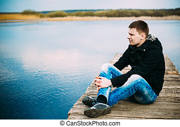 Young handsome man sitting on wooden pier, relaxing,...