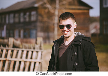 Young Handsome Man Staying Near Old Wooden House In Autumn...