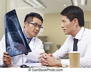 asian doctor and patient - asian doctor talking to patient...