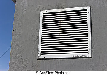 Vent window on gray concrete wall with blue sky
