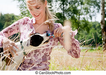 Playing with the toy - Blond girl and a american bulldog in...