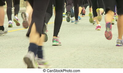 Marathon Runners - Close low angle reverse shot of runners...