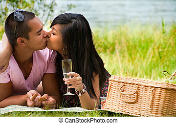 Kissing near the lake - Young happy asian couple enjoying...