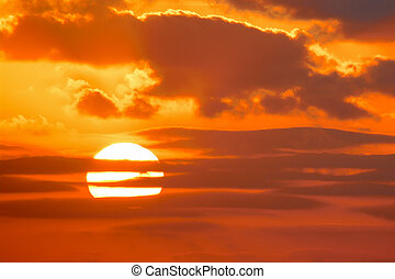 bright sun in an orange sky with dark clouds at sunset