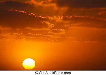 shining sun in an orange sunset - bright sun in an orange...