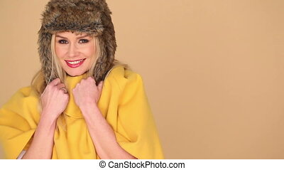 Pretty Woman in Yellow Fashion with Furry Hood - Side View...