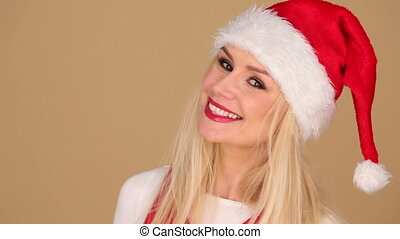 Cheerful blond woman wearing Santa hat - Beautiful cheerful...