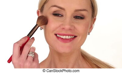 Happy attractive woman applying blusher to her cheek with a...